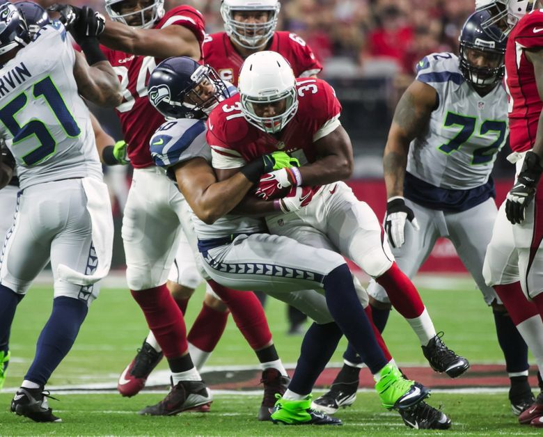 Seahawks linebacker K.J. Wright holds Cardinals running back David Johnson to a gain of 1 yard. (Bettina Hansen/The Seattle Times)