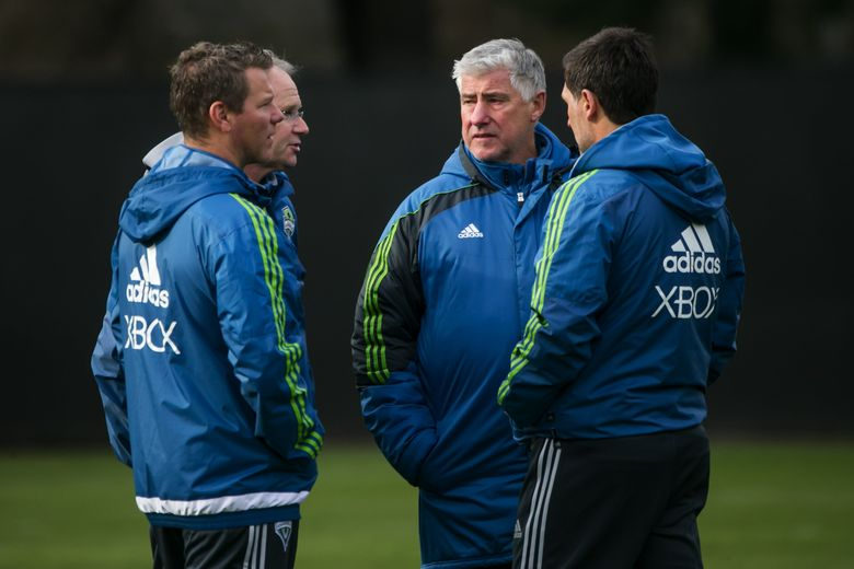 Departed Sounders coach Sigi Schmid, second from right, confers with interim coach Brian Schmetzer, second from left, before the upheaval. (Bettina Hansen/The Seattle Times)