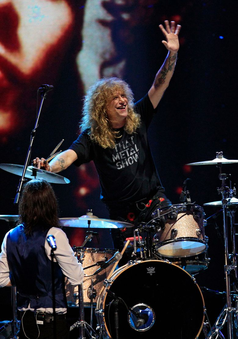 FILE –  In this April 15, 2012, file photo, drummer Steven Adler waves during a performance after Guns N' Roses' induction into the Rock and Roll Hall of Fame in Cleveland. Adler took the stage in Cincinnati Wednesday, July 6, 2016, to mark his first performance with the band fronted by Axl Rose in more than a quarter century. (AP Photo/Tony Dejak, File)