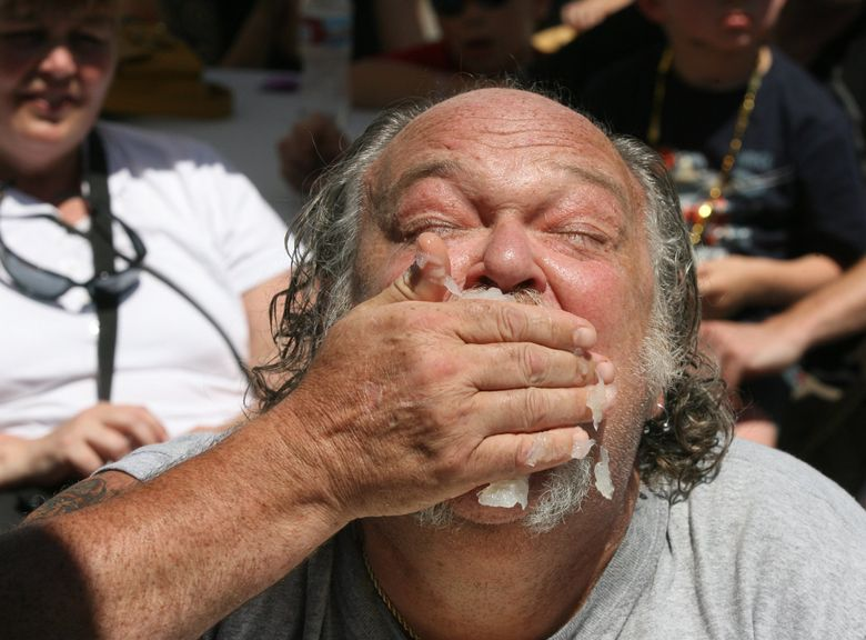 Steve Aarvik makes a wholehearted attempt to win the lutefisk-eating contest at a past Ballard SeafoodFest.  (Alan Berner/The Seattle Times)
