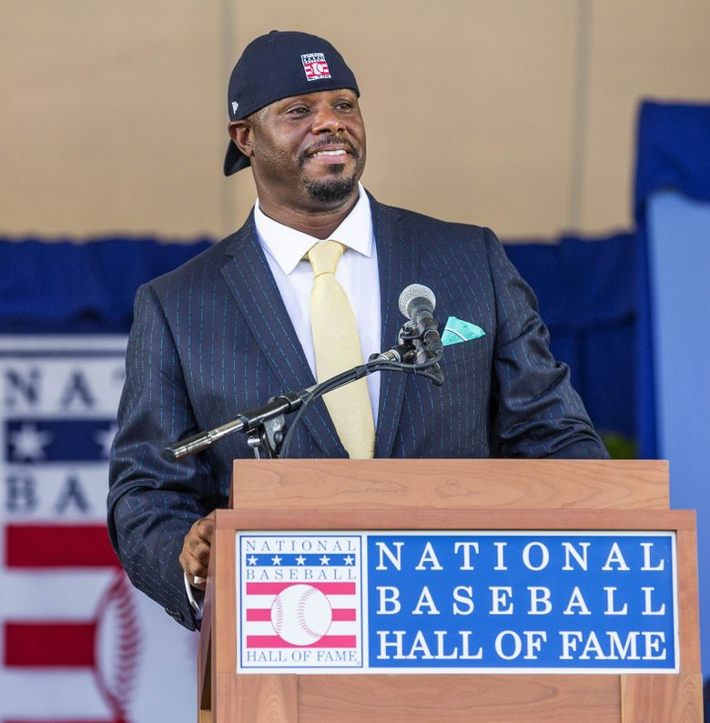 For his last act, Ken Griffey Jr. dons his hat backward at the conclusion of his speech at the Baseball Hall of Fame induction ceremony Sunday. (Dean Rutz/The Seattle Times)