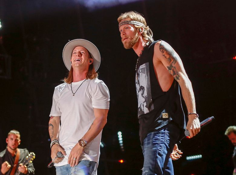 """FILE – In this June 11, 2016 file photo, Tyler Hubbard, left, and Brian Kelly of Florida Georgia Line perform at the CMA Music Festival in Nashville, Tenn. The country duo said it was misunderstanding after police agencies in two states said the duo didn't want any armed officers backstage during their shows. They said in a statement Tuesday, July 26, it was """"redundant for us to use local authorities"""" when security was already present and said they have an enormous amount of respect for police. (Photo by Al Wagner/Invision/AP, File)"""