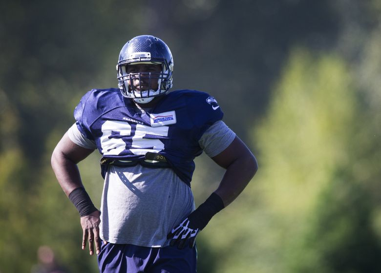 Seahawks center Patrick Lewis gets ready for another drill with Seahawks quarterback Russell Wilson. (Lindsey Wasson / The Seattle Times)