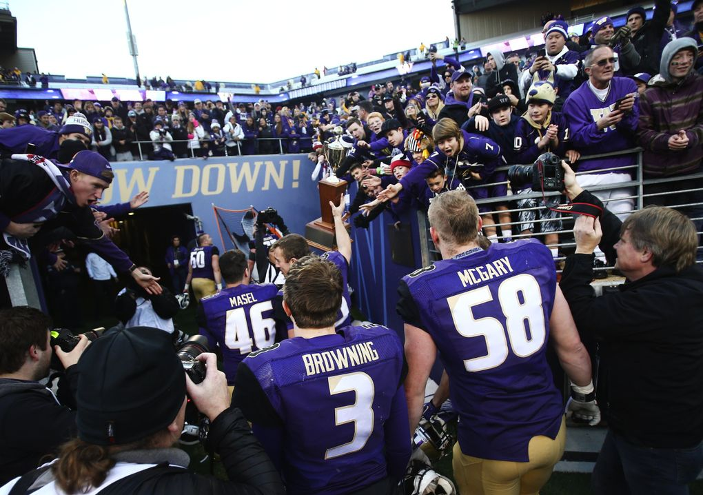 Washington quarterback Jake Browning (3) walks off the field with Washington offensive lineman Kaleb McGary as fans cheer while they try to touch the Apple Cup trophy during the 108th Apple Cup at Husky Stadium on Friday, Nov. 27, 2015. Washington beat Washington State 45-10.   (Lindsey Wasson / The Seattle Times)