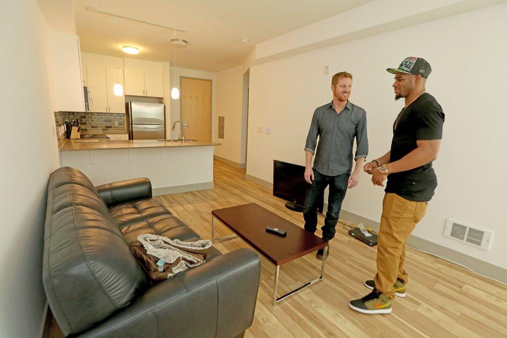Matt Calkins, left, and Zac Brooks go over Matt's new apartment for interior design advice. (Greg Gilbert / The Seattle Times)