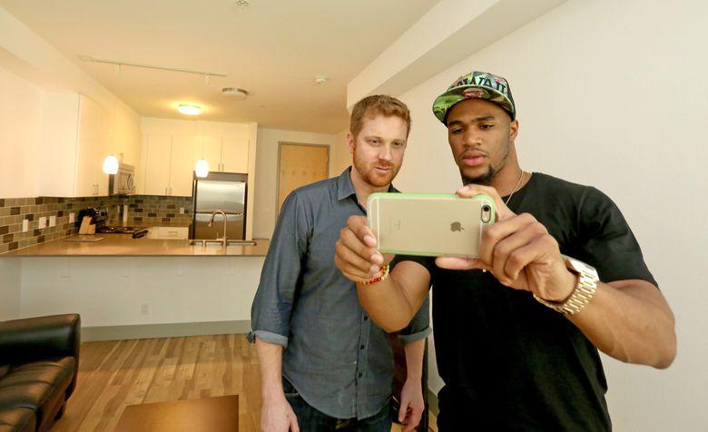 Sports columnist Matt Calkins, left, watches as Seahawks rookie Zac Brooks takes interior photos of Matt's new apartment. (Greg Gilbert / The Seattle Times)