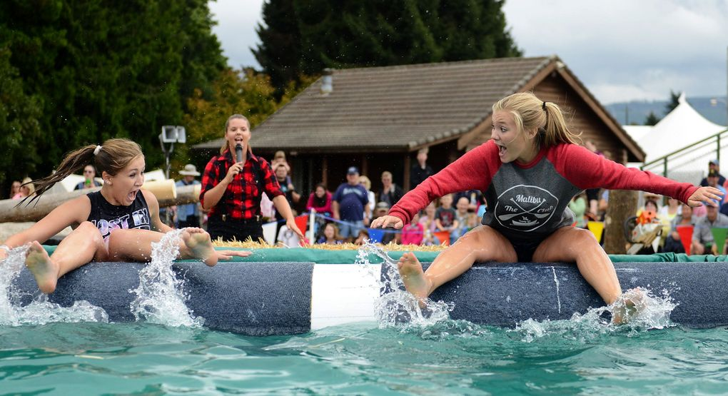Sydney Todd and Synnova Eide scream as they fall backwards off a log during the International Lumberjack Show at the Evergreen State Fair.  (Lindsey Wasson / The Seattle Times)