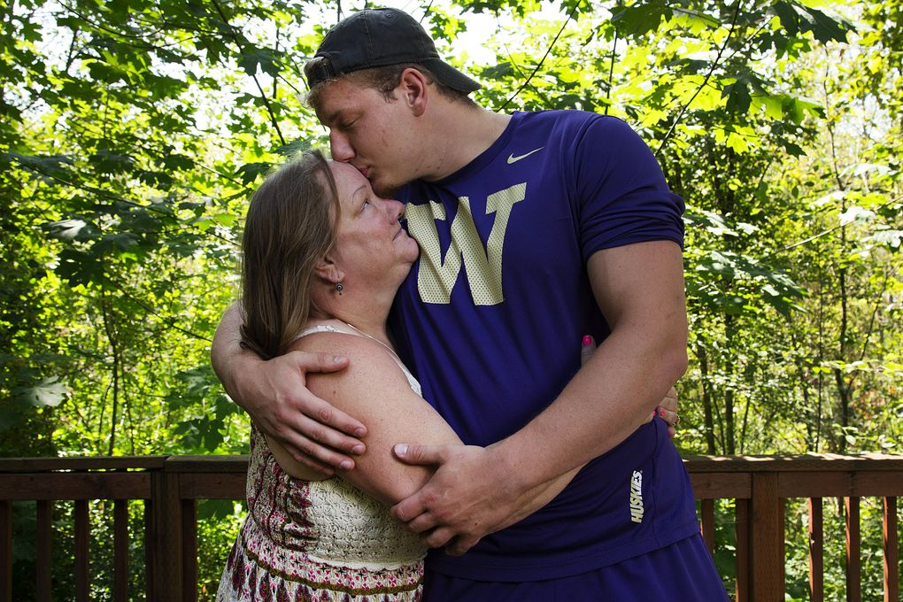 University of Washington offensive lineman Kaleb McGary kisses his mother, Cassandra McGary, on the forehead on the Hylebos Wildlife Trail in Fife earlier this month. (Johnny Andrews/The Seattle Times)