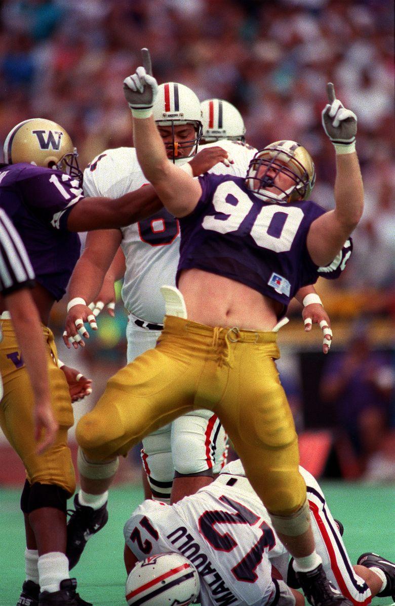UW's Steve Emtman celebrates a crushing tackle of Arizona quarterback George Malauulu during the Huskies' 54-0 defeat of Arizona on Oct. 5, 1991. (Mark Harrison/The Seattle Times)
