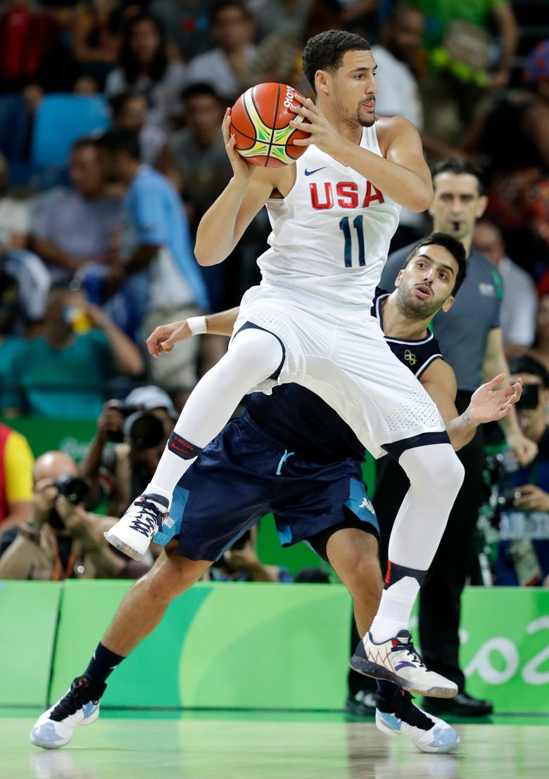 Former Washington State star Klay Thompson of the U.S. team passes over Argentina's Facundo Campazzo during a quarterfinal game Wednesday. The U.S. won 105-78. (Charlie Neibergall/AP)