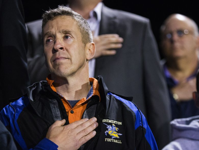 Coach Joe Kennedy listens to the national anthem during a Bremerton football game last fall. Kennedy has filed suit against the Bremerton School District, which suspended him after he refused orders to stop praying with players at games. (Lindsey Wasson/The Seattle Times)