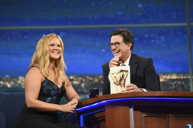 """This Aug. 22, 2016 photo released by CBS shows comedian Amy Schumer, left, with host Stephen Colbert on """"The Late Show with Stephen Colbert,"""" in New York. Schumer says she was hospitalized this summer with bronchitis in Hawaii while shooting a film with Goldie Hawn. As a guest on """"The Late Show With Stephen Colbert,"""" Schumer said she had difficulty speaking, was bedridden and coughed so much that she fractured some ribs.  (Timothy Kuratek/CBS via AP)"""