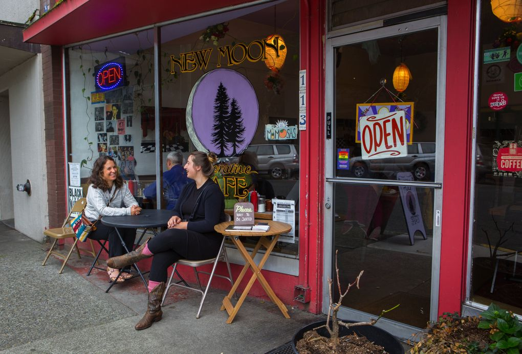 Brandi Hughes, left, and Jenny Slocum wait for a table at the New Moon Cooperative Cafe in Olympia. The cafe is owned and managed by its workers. (Ellen M. Banner/The Seattle Times)