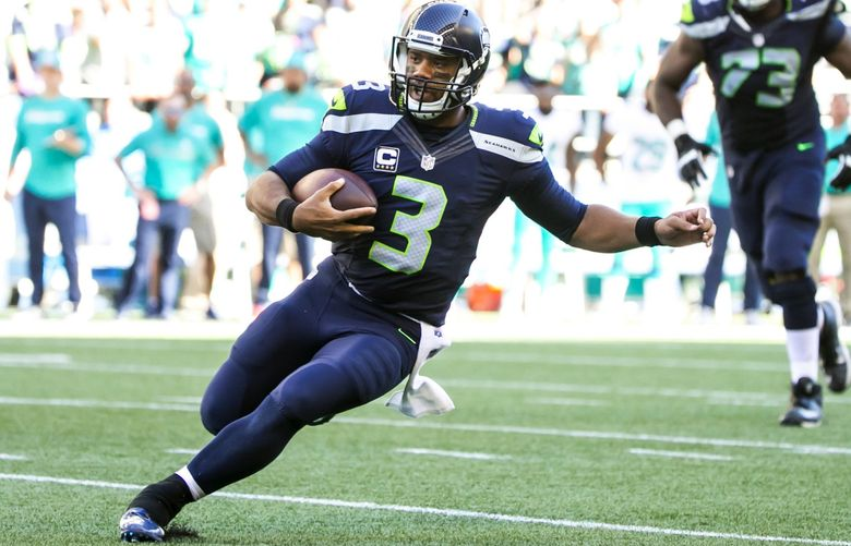 Seahawks quarterback Russell Wilson scrambles for a four-yard gain on their fourth quarter drive as the Seattle Seahawks take on the Miami Dolphins at CenturyLink Field Sept. 11, 2016.   (Bettina Hansen / The Seattle Times)