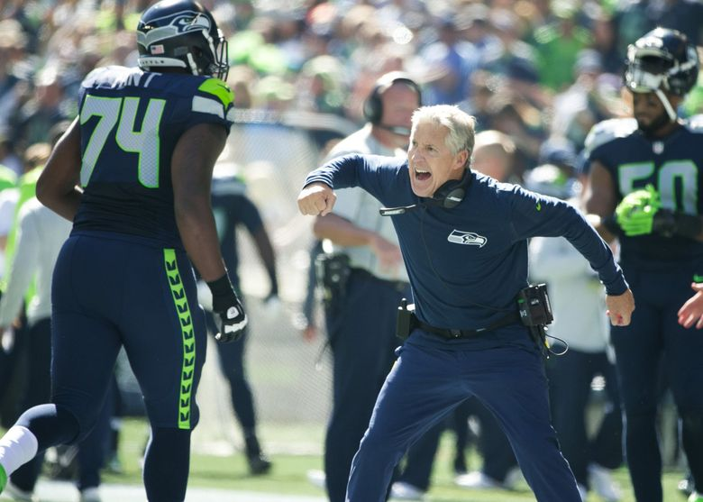 Seahawks coach Pete Carroll celebrates the second touchdown of the game with Seattle Seahawks tackle George Fant as the Seattle Seahawks take on the San Francisco 49ers  at CenturyLink Field. (Bettina Hansen / The Seattle Times)