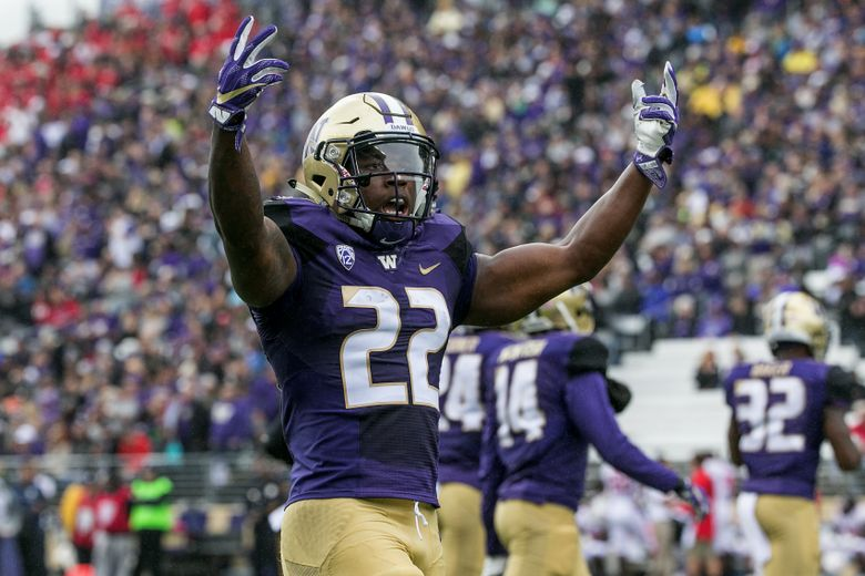 Washington running back Lavon Coleman tries to get the crowd riled up after his team scored a second touchdown in the first quarter of a game against Rutgers on Saturday, Sept. 3, 2016, at Husky Stadium in Seattle.