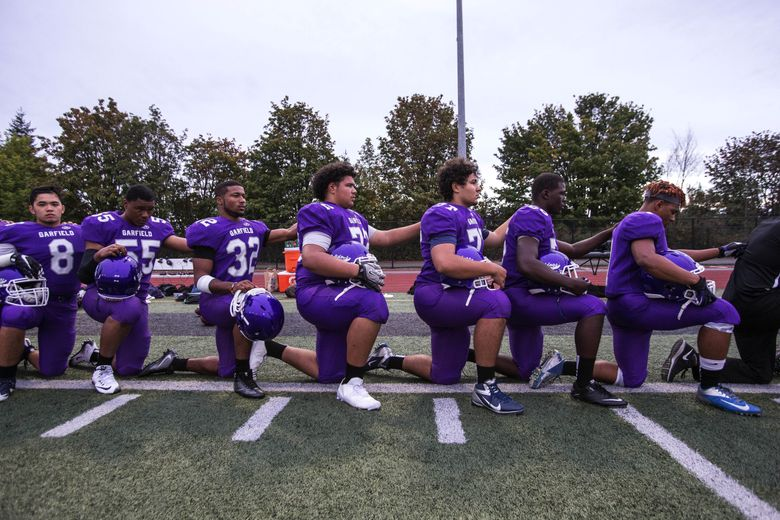 The entirety of the Garfield Bulldog football team – coaches and players – take a knee during the National Anthem Friday at the Southwest Athletic Complex.  Visiting Garfield played West Seattle in WIAA Football Friday, September 16, 2016, at the Southwest Athletic Complex. (Dean Rutz / The Seattle Times)