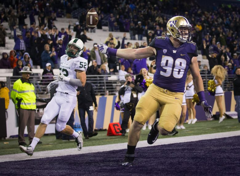Washington tight end Will Dissly flips the ball up as he scores on a 27 yard touchdown pass from Washington quarterback K.J. Carta-Samuels in the fourth quarter.  (Lindsey Wasson / The Seattle Times, 2016)