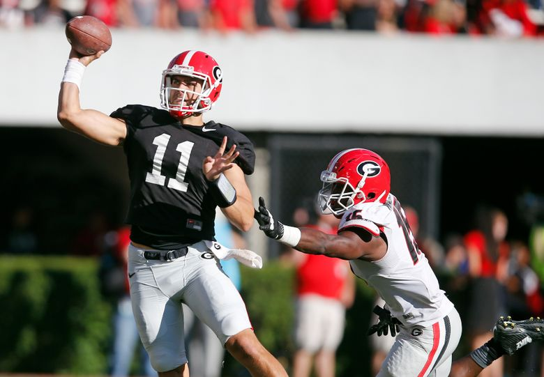 FILE – In this April 16, 2016, file photo, Georgia quarterback Greyson Lambert (11) throws under pressure from linebacker D'Andre Walker (15) during the second half of the NCAA college football team's spring game, in Athens, Ga. (AP Photo/John Bazemore, File)