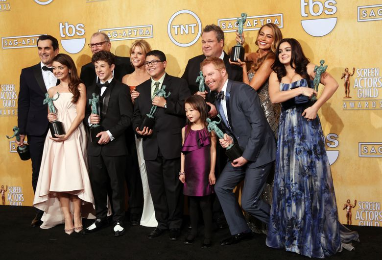 """FILE – In this Jan. 18, 2014, file photo, the cast of """"Modern Family"""" poses with their awards for outstanding performance by an ensemble in a comedy series fat the 20th annual Screen Actors Guild Awards at the Shrine Auditorium in Los Angeles. ABC has confirmed that a transgender child actor will guest star on the series in an episode set to air Wednesday, Sept. 28, 2016. (Photo by Matt Sayles/Invision/AP, File)"""