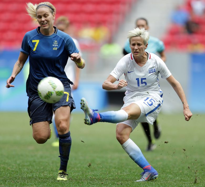 """FILE – In this Aug. 12, 2016, file photo, United States' Megan Rapinoe kicks the ball past Sweden's Lisa Dahlkvist during a quarterfinal match of the women's Olympic football tournament in Brasilia. The Washington Spirit prevented Seattle midfielder Megan Rapinoe from kneeling again during the national anthem by altering its pregame ceremonies rather than """"subject our fans and friends to the disrespect we feel such an act would represent.""""  The National Women's Soccer League team moved up the anthem, Wednesday night, Sept. 7, 2016,  playing it while the teams were off the field at the Maryland SoccerPlex.  (AP Photo/Eraldo Peres, File)"""