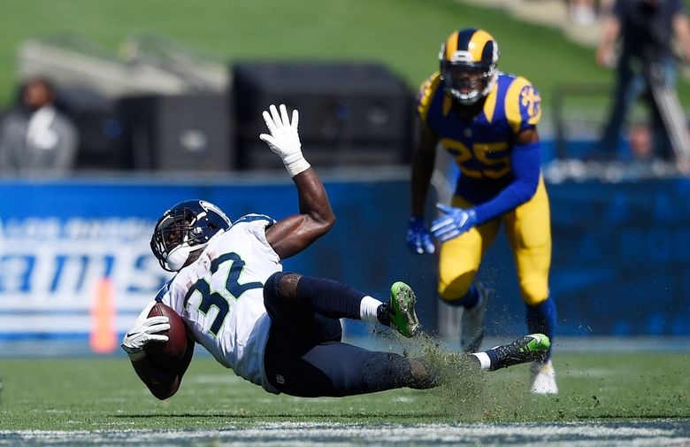 Christine Michael (32) of the Seahawks slips while carrying the ball in last Sunday's loss to the Los Angeles Rams. (Kelvin Kuo/AP)