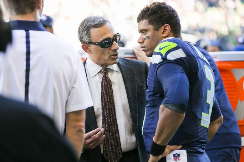 E. Edward Khalfayan, MD, an orthopedic surgeon and the Seahawks head team physician, talks with Seattle Seahawks quarterback Russell Wilson after he came out of the game with a knee injury as the Seattle Seahawks take on the San Francisco 49ers at CenturyLink Field in Seattle Sunday September 25, 2016.  (Bettina Hansen/The Seattle Times)