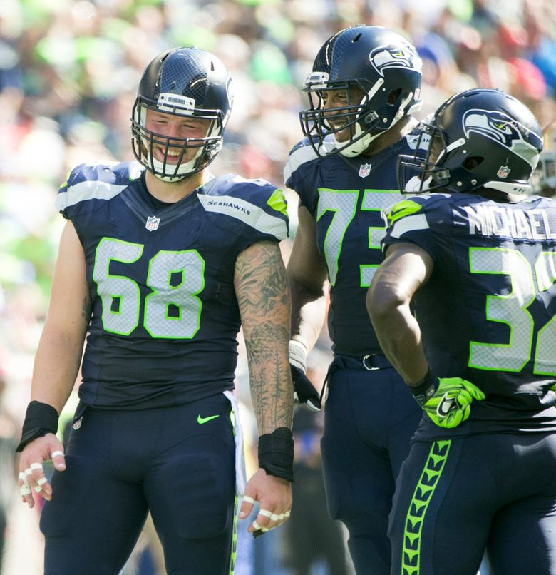 Seattle Seahawks center Justin Britt, left, Seattle Seahawks offensive guard J'Marcus Webb and Seattle Seahawks running back Christine Michael talk in between plays in the second quarter. (Bettina Hansen/The Seattle Times)