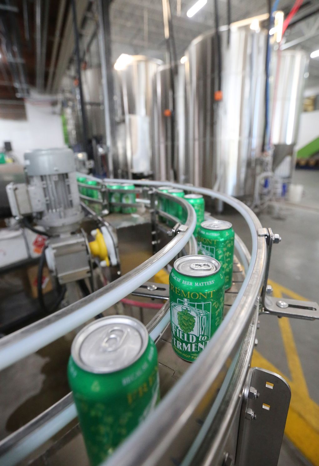"""At Fremont Brewing's facility in Ballard, cans of fresh-hop """"Field to Ferment"""" pale ale go flying by. (Greg Gilbert/The Seattle Times)"""