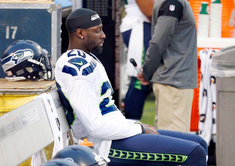 Seattle Seahawks cornerback Jeremy Lane sits as the national anthem plays before a preseason NFL football game against the Oakland Raiders. (AP Photo/Tony Avelar)
