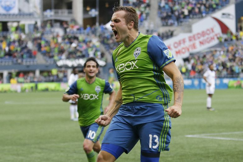 Seattle Sounders forward Jordan Morris, right, celebrates after he scored a goal against the Vancouver Whitecaps with assists from Nicolas Lodeiro, left, and Erik Friberg, not shown, in the second half of an MLS soccer match, Saturday, Sept. 17, 2016, in Seattle. The Sounders beat the Whitecaps 1-0. (AP Photo/Ted S. Warren)