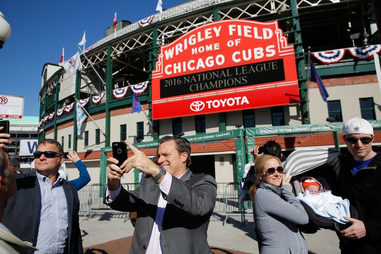 Fans take selfies under the marquee at Wrigley Field in October to mark the Cubs' National League Championship.  (Michael Tercha/Chicago Tribune via AP)