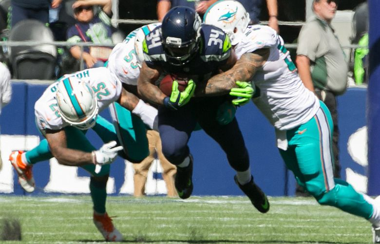 Seattle Seahawks running back Thomas Rawls b;as through Miami defenders in the second quarter as the Seattle Seahawks take on the Miami Dolphins at CenturyLink Field Sept. 11, 2016. (Bettina Hansen/The Seattle Times)