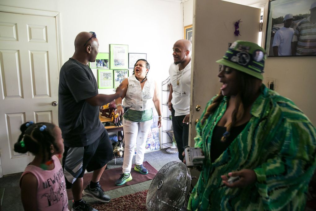 """Family and friends meet in the house where the Rawls family grew up, from left, Al Washington and his daughter Alyssa, 6, Veronica """"Aunt Tweety"""" Thompson, Thomas """"Rell"""" Rawls and Deadra Whitley. Washington coached """"Ty,"""" Thomas Rawls of the Seahawks, while he was a kid in Flint Youth Football, and Aunt Tweety was the one who encouraged the boys to join in the first place. The house belonged to """"Granny,"""" or Diane Rawls, Thomas """"Terrell"""" Rawls' mother, and Whitley lived next door, so their three kids could go between the two houses.  (Bettina Hansen/The Seattle Times)"""