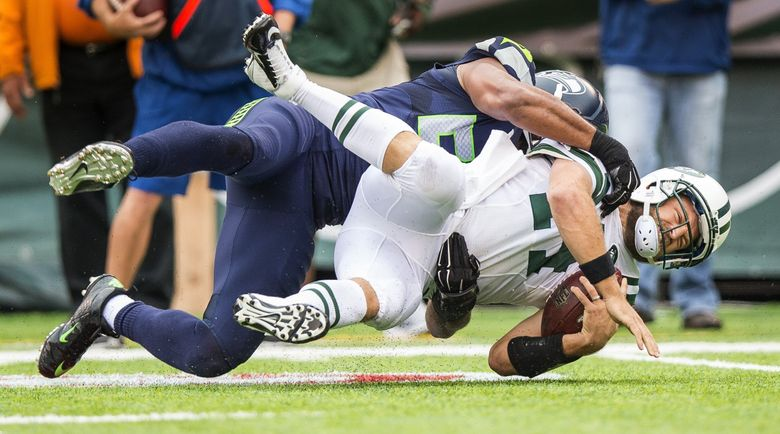 Seattle's KJ Wright drops Jets quarterback Ryan Fitzpatrick for a 4-yard loss in the 1st quarter Sunday.   (Dean Rutz / The Seattle Times)
