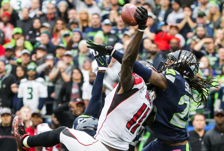 Seattle Seahawks free safety Earl Thomas and cornerback Richard Sherman stop a last-chance throw on fourth down to Atlanta Falcons wide receiver Julio Jones in the final minute as the Seattle Seahawks defeat the Atlanta Falcons 26-24 at CenturyLink Field on Sunday. (Bettina Hansen / The Seattle Times)