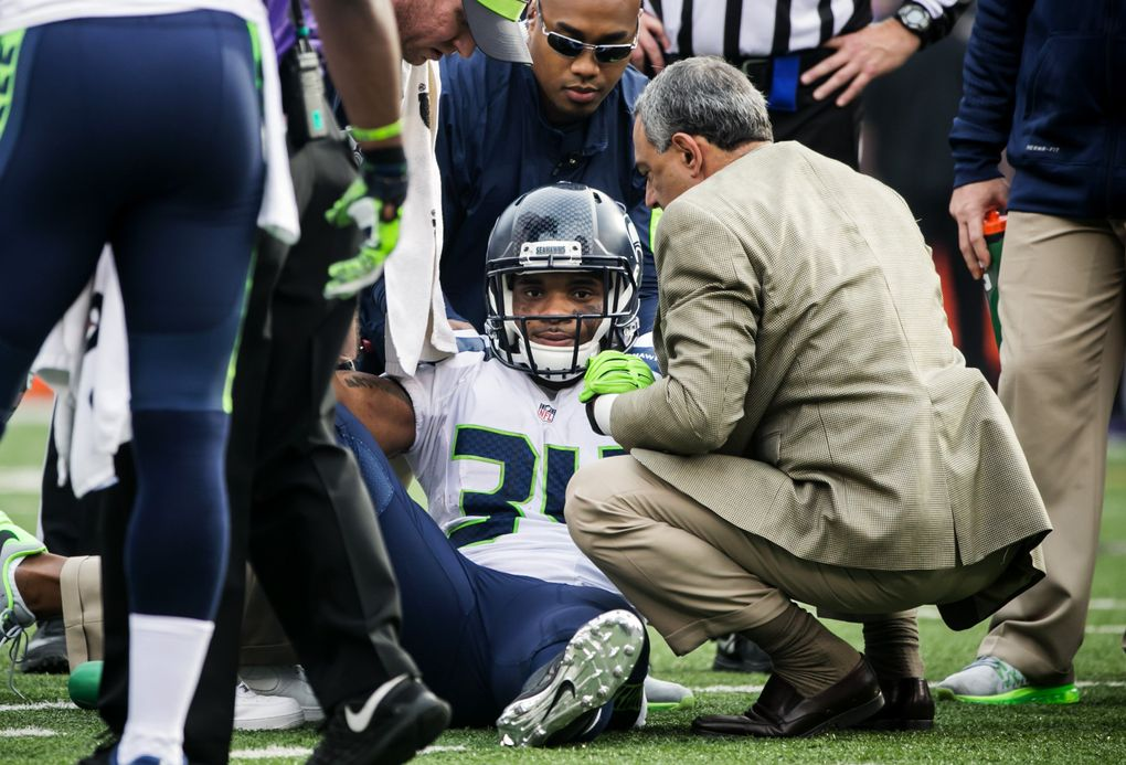 Seahawks running back Thomas Rawls is helped up after injuring his ankle in the first quarter of the Seahawks-Ravens game last December. (Bettina Hansen/The Seattle Times)