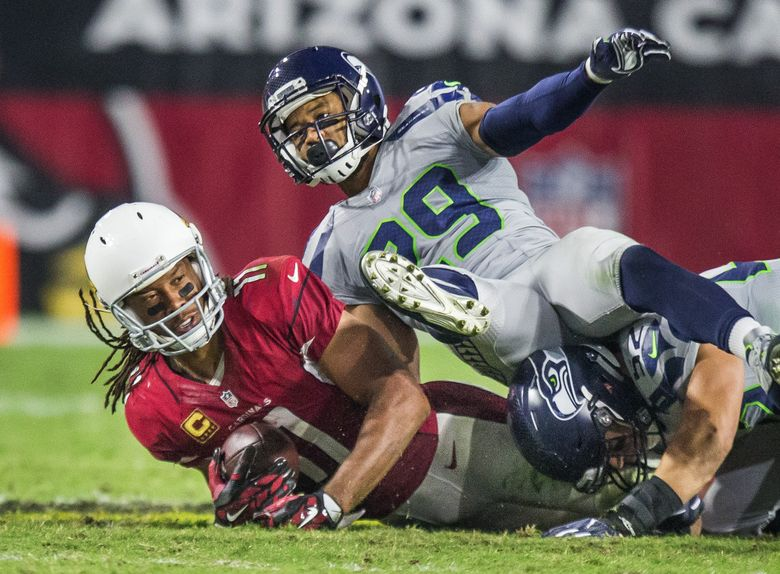 Seahawks free safety Earl Thomas knocks down Cardinals receiver Larry Fitzgerald on Sunday in Glendale, Ariz. (Dean Rutz / The Seattle Times)
