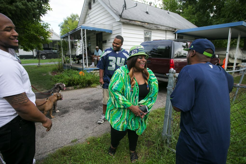 """Deadra Whitley talks to Derrin """"Uncle Duke"""" Rawls outside Granny's house on Foss Ave. in the north end of Flint, Mich. Her middle son Thomas """"Rell"""" Rawls is to the left, and his cousin Quientin Lee is behind her. Diane Rawls, known as Granny, owned the house for decades until she died earlier this year. Deadra's kids grew up in Granny's house with their father and she lived in the house next door.  (Bettina Hansen/The Seattle Times)"""