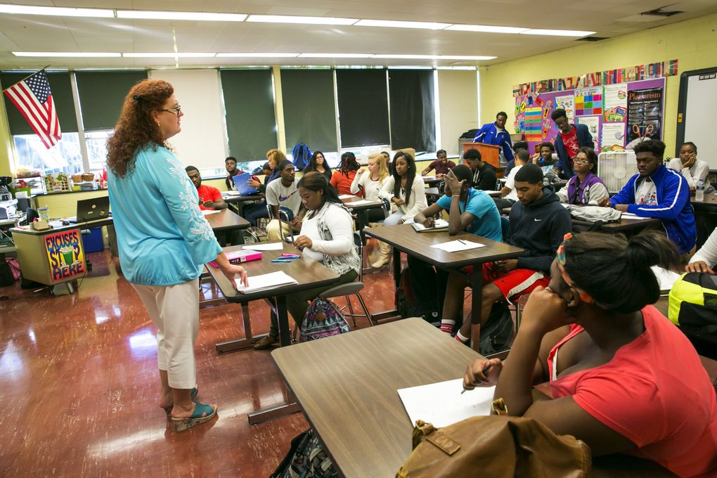 """Jeanette Rousseau, known as """"Miss J,"""" leads a class at Flint Southwestern Academy High School. She's known as a tough-love teacher, but was Thomas Rawls' favorite when he was in high school. """"Every time I would talk to him about something I would equate it to football, because that's what he knew,"""" she said. After he missed a qualifying score on a standardized test several times in a row that he needed to make it into the University of Michigan, she tutored him for two weeks straight to prepare. """"That was his gateway for a scholarship to college,"""" she said. """"I always tell my students – I can't take credit for his success. I gave him the tools he needs to be successful – but I give every student in my classroom the tools they need to be successful.""""  (Bettina Hansen/The Seattle Times)"""