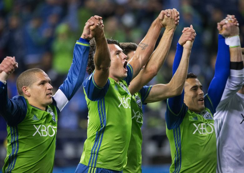 Sounders forward Nelson Valdez (16), center, celebrates winning against Sporting Kansas City in a Western Conference knockout round game at CenturyLink Field on Thursday. The Sounders won 1-0 on a late goal from Valdez to advance.  (Lindsey Wasson/The Seattle Times)