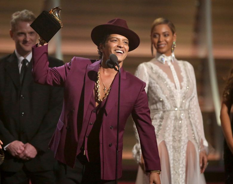 """FILE – In this Feb. 15, 2016 file photo, Bruno Mars accepts the award for record of the year for """"Uptown Funk"""" at the 58th annual Grammy Awards in Los Angeles. The Grammy-winning star said in an interview with The Associated Press he wrote """"24K Magic"""" around the time """"Uptown Funk"""" topped the Billboard Hot 100 chart last year. """"24K Magic"""" debuted at No. 5 on the Hot 100 chart this week. (Photo by Matt Sayles/Invision/AP, File)"""