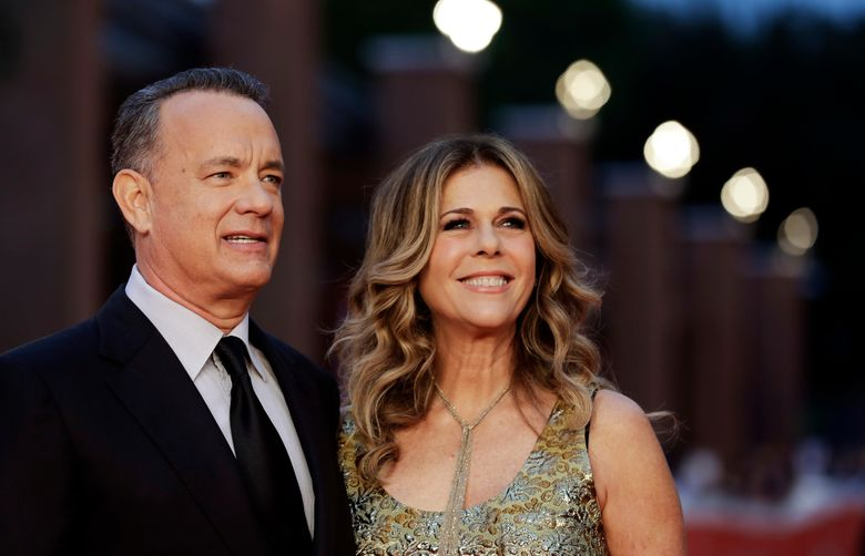 """FILE – In this Thursday, Oct. 13, 2016, file photo, Actor Tom Hanks, left, flanked by his wife Rita Wilson, arrives to receive a lifetime achievement at the Rome Film Festival, in Rome. Ever since her husband, Hanks, appeared on """"Saturday Night Live"""" as the strange man in the pumpkin suit in that haunted elevator, Saturday, Oct. 22, Wilson has received all sorts of crazy David S. Pumpkins things, including clips, texts and gifts. (AP Photo/Andrew Medichini, File)"""