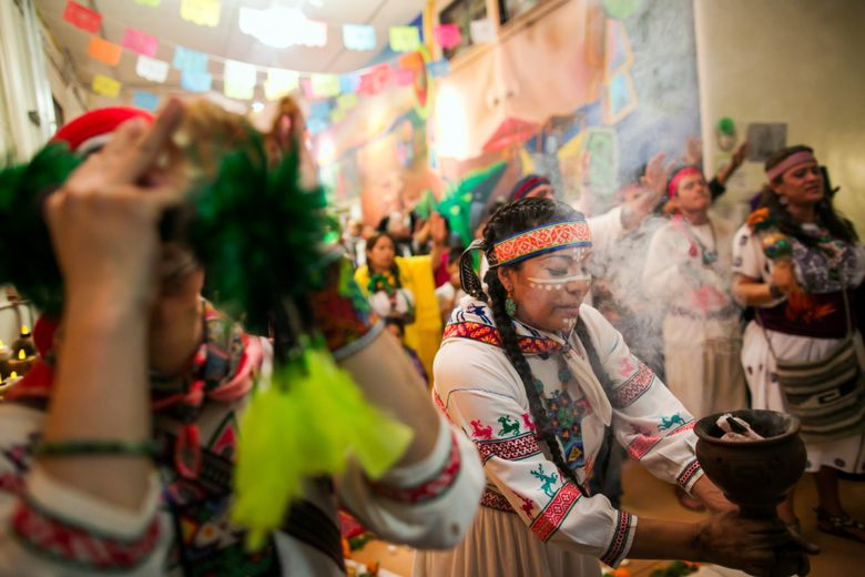Araceli Jaime, a member of Ce Atl Tonalli, an Aztec dance group, uses a popoxcomitl, a jar containing burning copal, an aromatic tree resin used in ancient Aztec rituals, to fill the air with smoke as they sing during the prayer ceremony at the Dí'a de los Muertos celebration, at the El Centro de la Raza, in Seattle, on Nov. 1, 2013.   (Marcus Yam/The Seattle Times)
