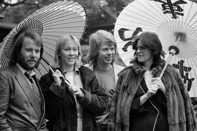 """FILE – In this March 14, 1980, file photo, the four members of the Swedish pop group ABBA hold Japanese oil paper parasols in a light rain in the Japanese garden of their hotel in Tokyo. From left: Benny Andersson, Agnetha Faltskog, Bjorn Ulvaeus and Anni-Frid Lyngstad. The members of ABBA are reuniting for a """"new digital experience"""" next year. The iconic Swedish pop band made the announcement Wednesday, Oct. 26, 2016, but didn't offer much detail. (AP Photo/Tsugufumi Matsumoto)"""