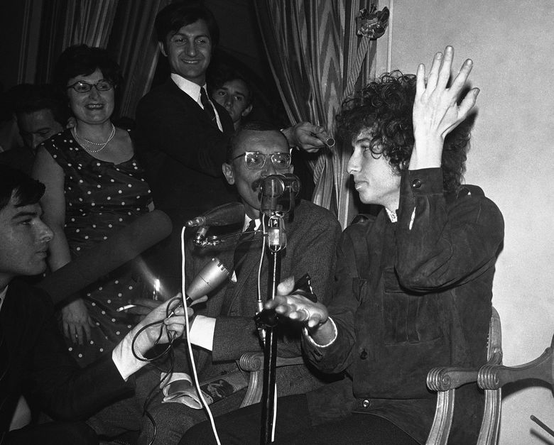 """FILE – In this May 22, 1966, file photo, Bob Dylan gestures during a news conference in Paris, France. Dylan won the 2016 Nobel Prize in literature on Thursday, Oct. 13, 2016, a stunning announcement that for the first time bestowed the prestigious award on a musician for """"having created new poetic expressions within the great American song tradition."""" (AP Photo/Pierre Godot, File)"""