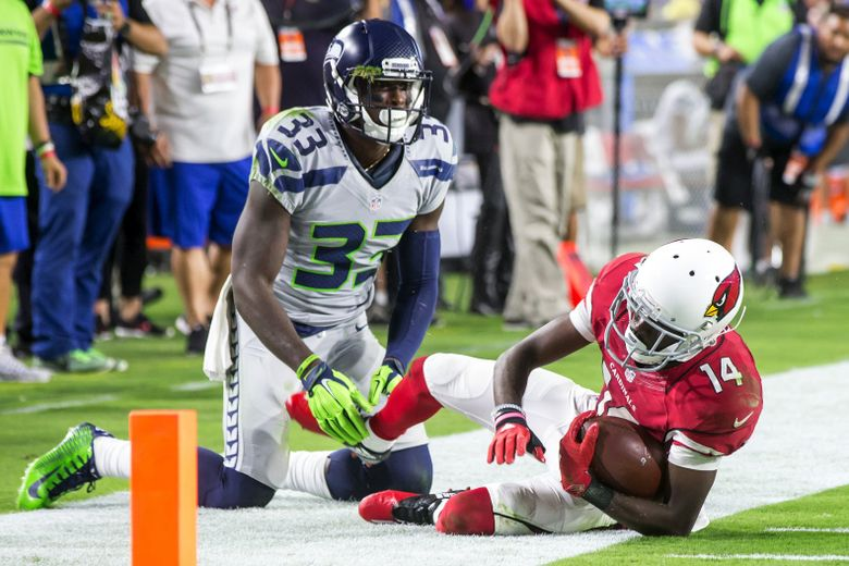 Seattle safety Kelcie McCray (33) didn't give up when Arizona's J.J. Nelson (14) was racing toward the end zone on what was a 40-yard gain in overtime. McCray hustled to stop Nelson at the 5-yard line, and he was rewarded when the Cardinals ended up not scoring on the drive. (Bettina Hansen/The Seattle Times)