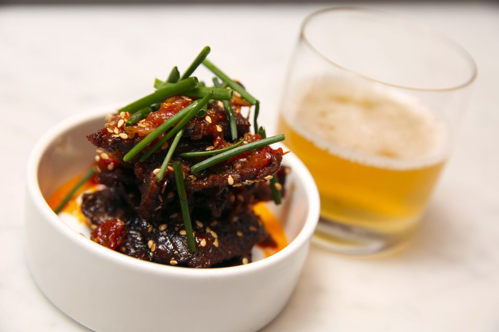 """A snack at Heartwood Provisions: wagyu """"beef jerky"""" glazed with a sweet-hot chile preserve, paired with a ale and dry vermouth cocktail. (Ken Lambert/The Seattle Times)"""