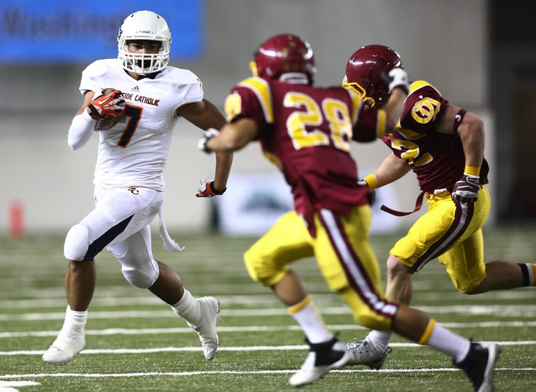 Eastside Catholic's Brandon Wellington tries to avoid Kaleb Swain (28) of O'Dea in the first quarter of the Class 3A state semifinals in 2013. Eastside Catholic won that game 28-14.