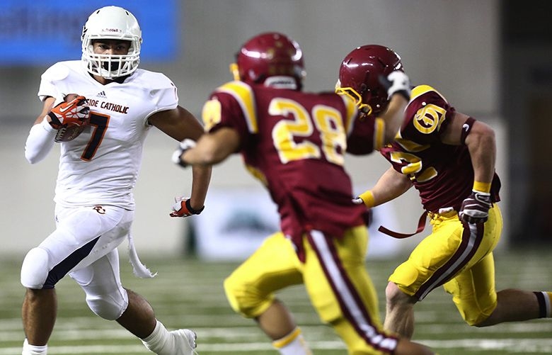 11/29/2013 134557 3A FOOTBALL SEMIFINALS Eastside Catholic's Brandon Wellington tries to avoid Kaleb Swain (28) of O'Dea in the first quarter of the 3A state semifinal game at the Tacoma Dome Friday, Nov. 29, 2013. Eastside Catholic led at the half, 21-7.